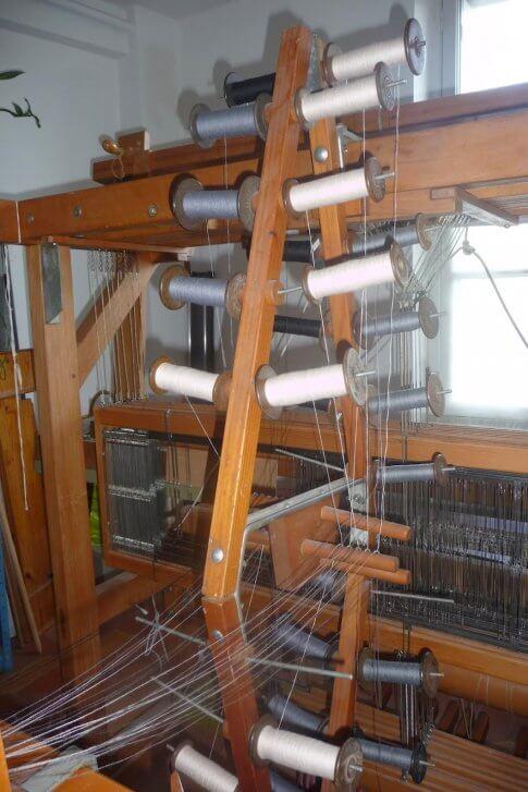 Les fils sont enroulés sur des bobines posées sur le cantre dans l'ordre des couleurs